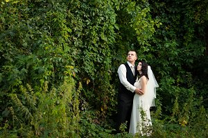 Newlyweds stand in the high grass