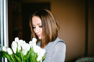 A girl holds a bouquet of white tulips