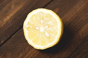 Half lemon on wooden table.
