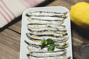 Close-up of anchovy dish with olive oil, vinegar and lemon.