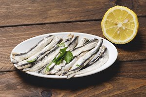 Plate of anchovies with olive oil, vinegar and lemon. Half lemon.
