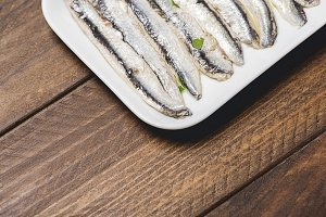 Close-up of tasty anchovies on a white tray on a brown wooden table.