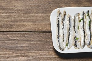 Close-up of tasty anchovies on a white tray on a brown wooden table. Horizontal shoot.
