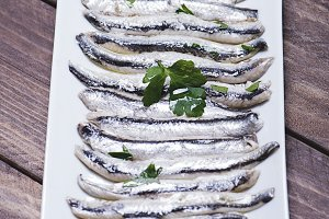 Tasty anchovies on a white tray on a brown wooden table. Vertical shoot.
