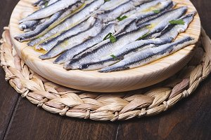 Exquisite marinated anchovies with olive oil and vinegar on brown wooden table. Horizontal shoot.