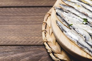 Exquisite marinated anchovies with olive oil and vinegar on brown wooden table. Copy-space.