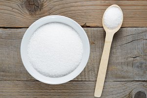 Sugar in bowl and spoon on table