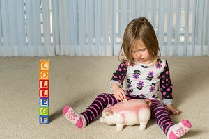 Young toddler putting money for college in bank