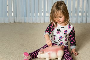 Young toddler putting money into large pottery piggy bank