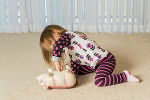 Young toddler getting money from pottery piggy bank