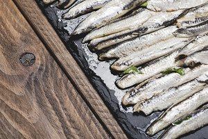 Anchovies with olive oil and vinegar on a plate of slate on wooden table. Food.