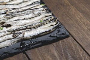 Anchovies with olive oil and vinegar on a plate of slate on wooden table. Food. Horizontal shoot.