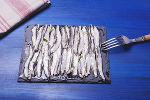 Anchovies with olive oil and vinegar on a plate of slate on blue wooden table next to a fork and a napkin. Food. Horizontal shoot.