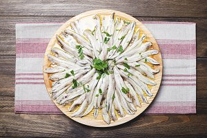 Anchovies with olive oil and vinegar on a wooden plate on a tablecloth. Food. Horizontal shoot.