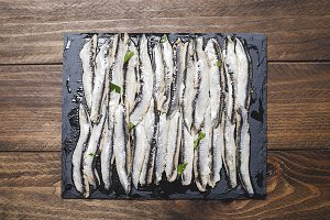 View from above of anchovies with olive oil and vinegar on a slate dish on a brown wooden table. Food Horizontal shoot.