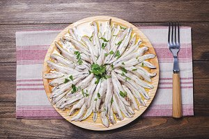 Anchovies with olive oil and vinegar on a wooden plate on a tablecloth next to a fork. Food.