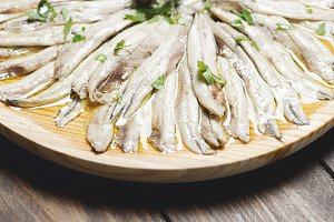 Close-up of anchovies with olive oil and vinegar on a wooden plate on a brown wooden table. Healthy food.