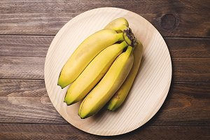 Bananas on a wooden plate. Food. Horizontal shoot.