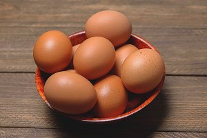 Brown wooden bowl with eggs.