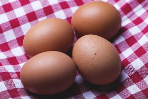 Eggs on red and white tablecloth. Horizontal shoot.