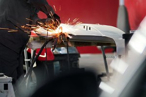 Professional car service - worker grinding metal construction with a circular saw