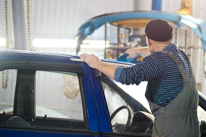 Professional car service - a worker polishes blue automobile