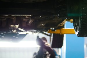 Automobile diagnostic - mechanic working under a lifted car, de-focused background
