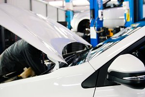 Open the hood of the car - the engine, the battery, the injector - mechanic working in the automotive service