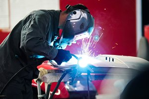 Welding industrial: worker in helmet repair detail in car auto service - blue sparklers