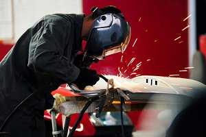 Welding industrial: worker in helmet repair detail in car auto service