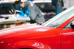 Welding industrial: worker in helmet repair detail in auto service in front of the red car
