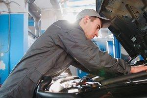 Mechanic in overalls working in the garage - repairing luxury SUV in front of sun