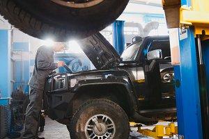 Luxury SUV standing in the garage for repairing - mechanic working