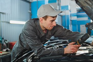 Mechanic in overalls looking to hood of the car - automobile service repairing