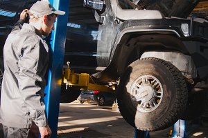 Mechanic lifts SUV in garage automobile service
