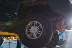 Luxury SUV in garage automobile service - wheel, close up
