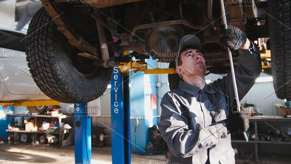 Garage automobile service - a mechanic checks the suspension