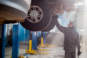 Garage automobile service - a mechanic checks the transmission