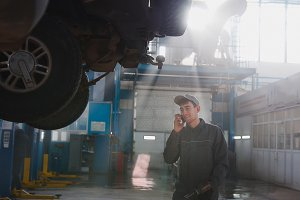 Garage automobile service - a mechanic near lifted car speaks on cellphone, telephoto