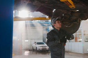 Garage automobile service - a mechanic under bottom of car checks the wheel