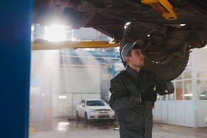 Garage automobile service - a mechanic under bottom of car checks the wheel