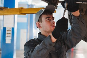 Garage automobile service - a mechanic under bottom of car checks the wheel, close up