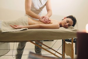Attractive young woman receiving massage at spa. Relaxation treatment for caucasian model