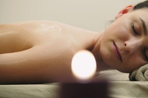 Young woman lying on massage table at spa salon