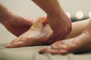 Sesame oil massage for foot. Relaxation treatment for young female, close up