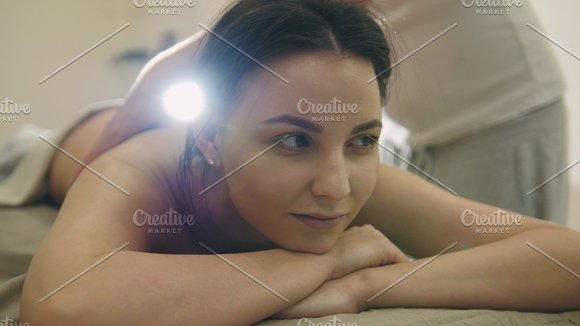 Massage parlor - attractive girl smiling and gets relaxing healing therapy, backlight
