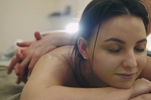 Massage parlor - young woman gets relaxing healing therapy for back