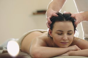 Massage parlor - young girl gets relaxing healing therapy for head