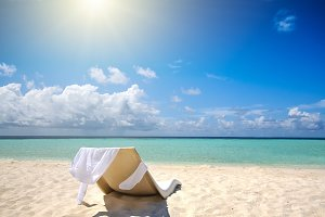 Single chair on the white sand beach. Vacation concept
