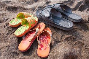 Three pairs of flip-flops on the sand